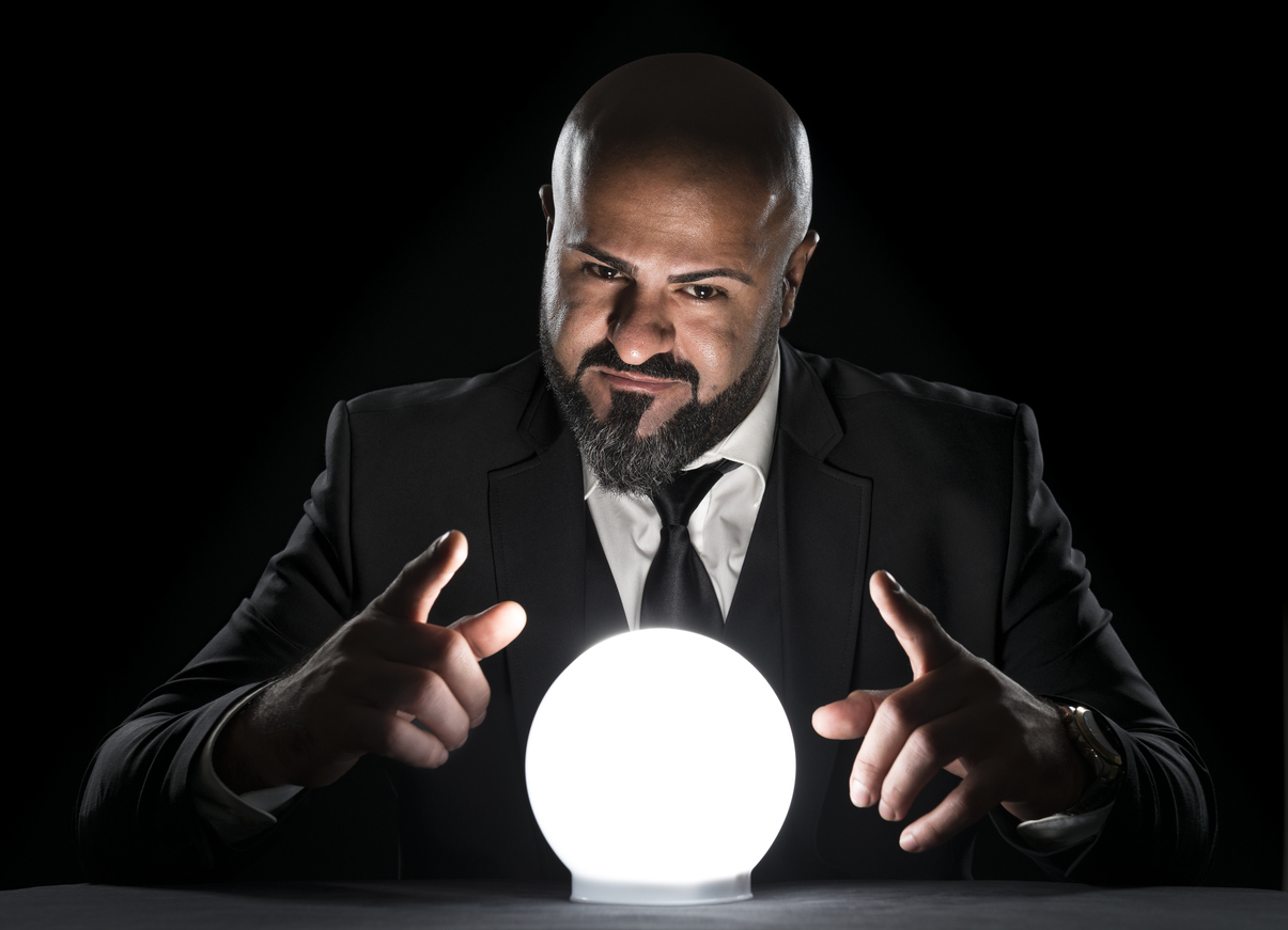 A fortune teller sitting at a desk gesturing at a glowing crystal ball. The bald man with the long beard