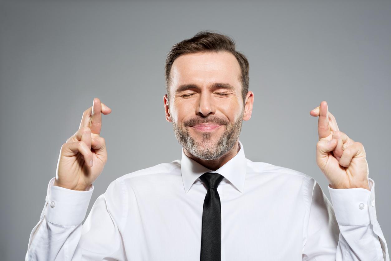 Portrait of businessman keeping his fingers crossed. Studio shot, grey background