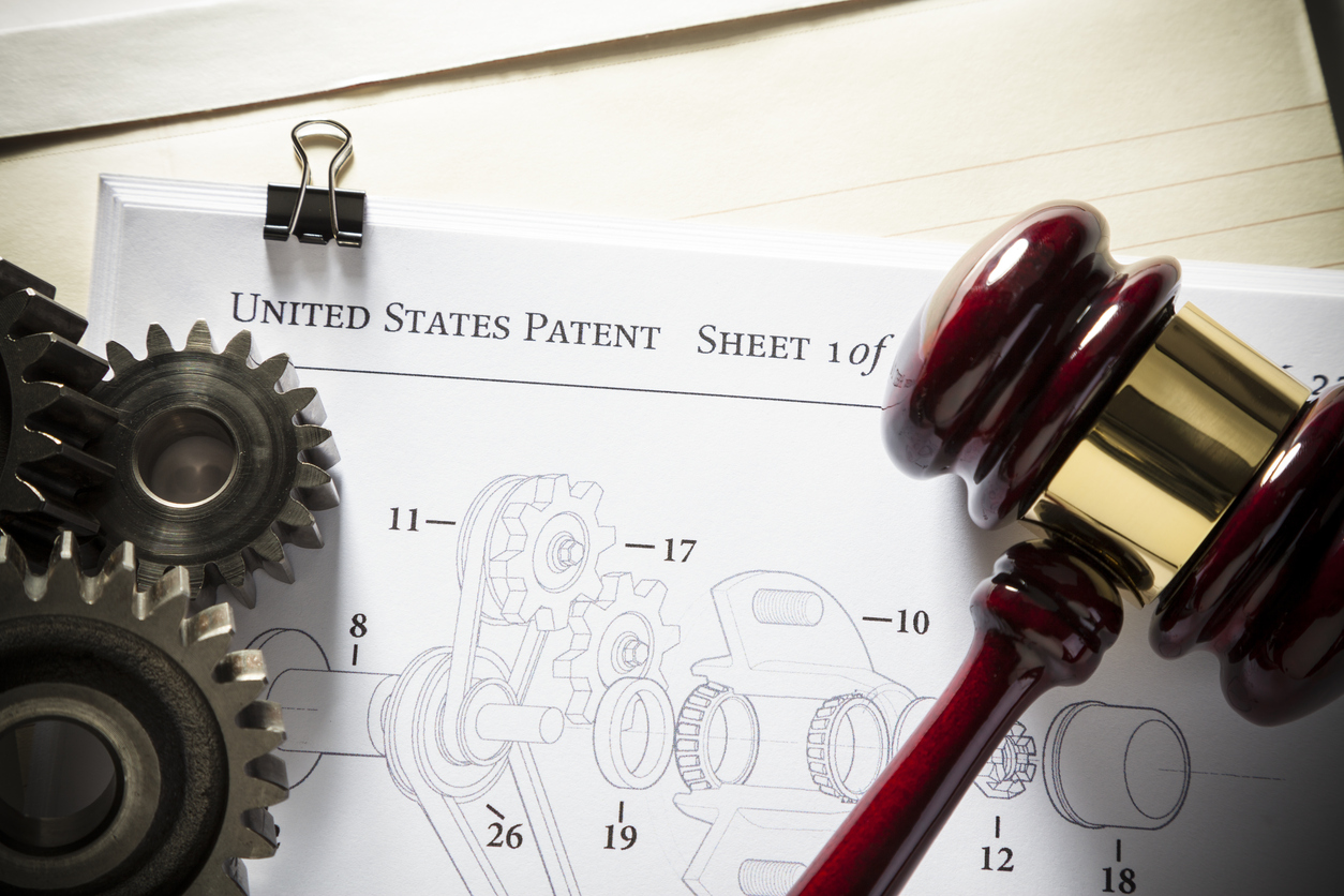 Gavel next to gears and mechanical diagram for patent application. Concept for patent attorney