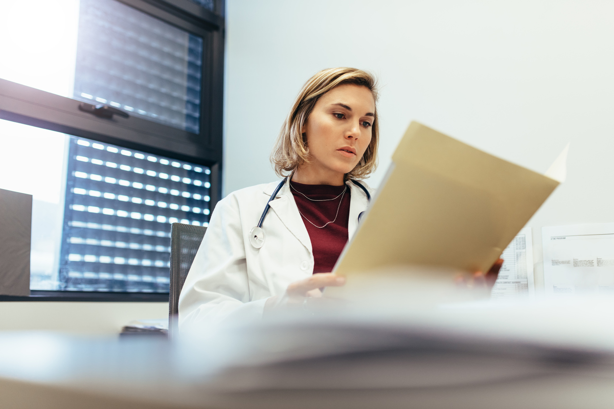 Female doctor sitting in her office and studying medical records. Medicine professional reading reports in clinic.