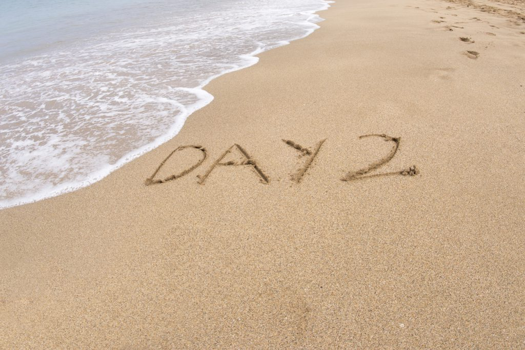 Day 2 is written on sand on a Hawaiian beach
