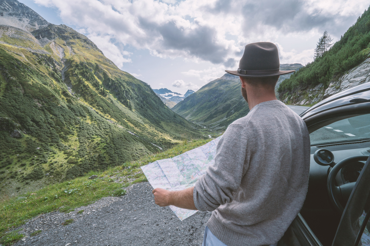 Young man looks at road map near on mountain road, Switzerland