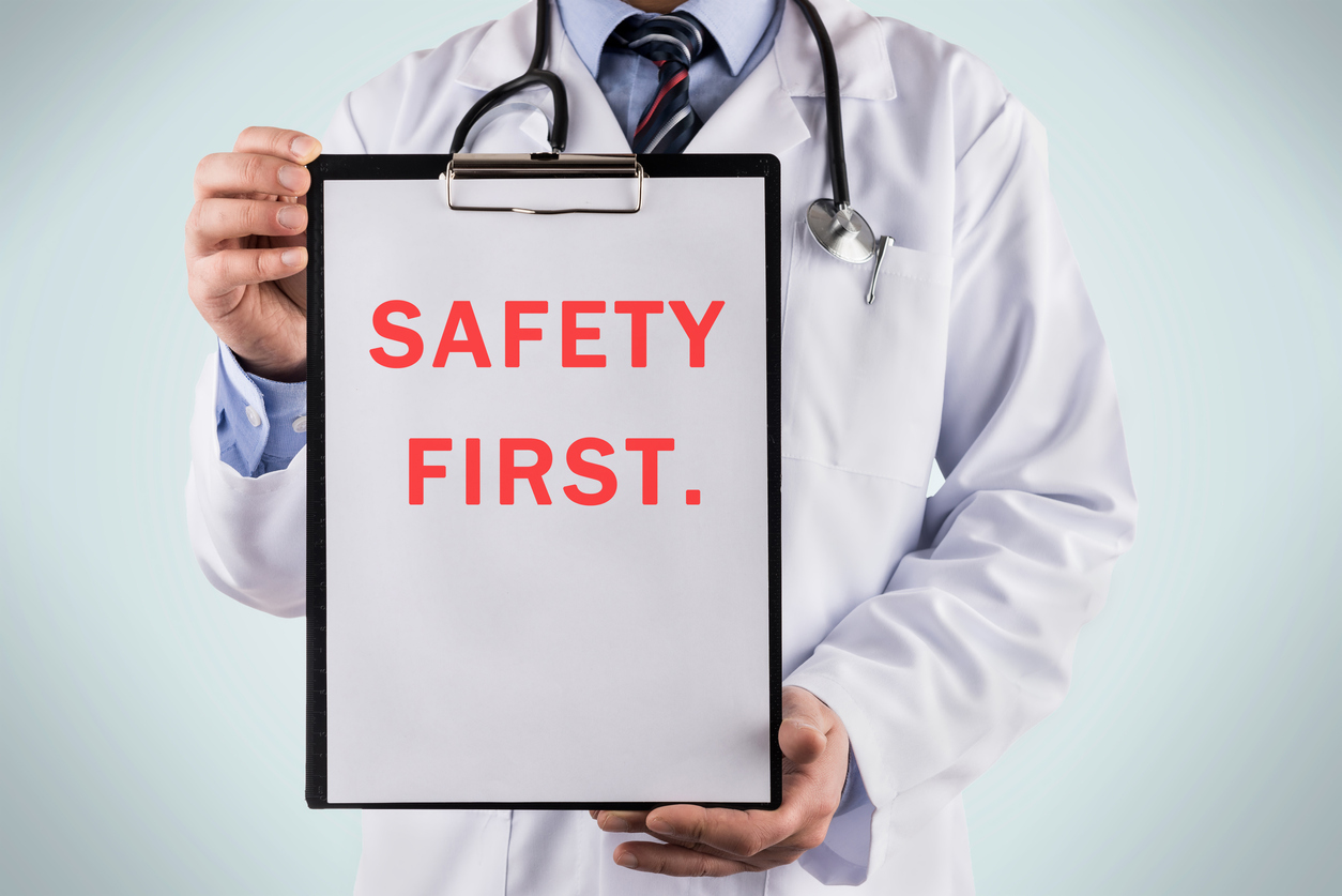 Doctor holding a clipboard with Safety first, Medical concept