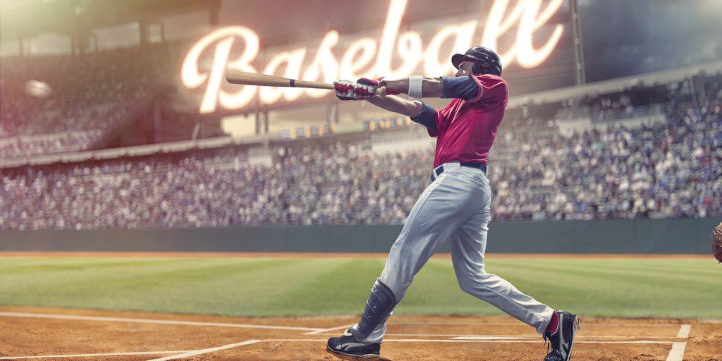Professional Baseball Batter Striking Baseball During Night Game In Stadium