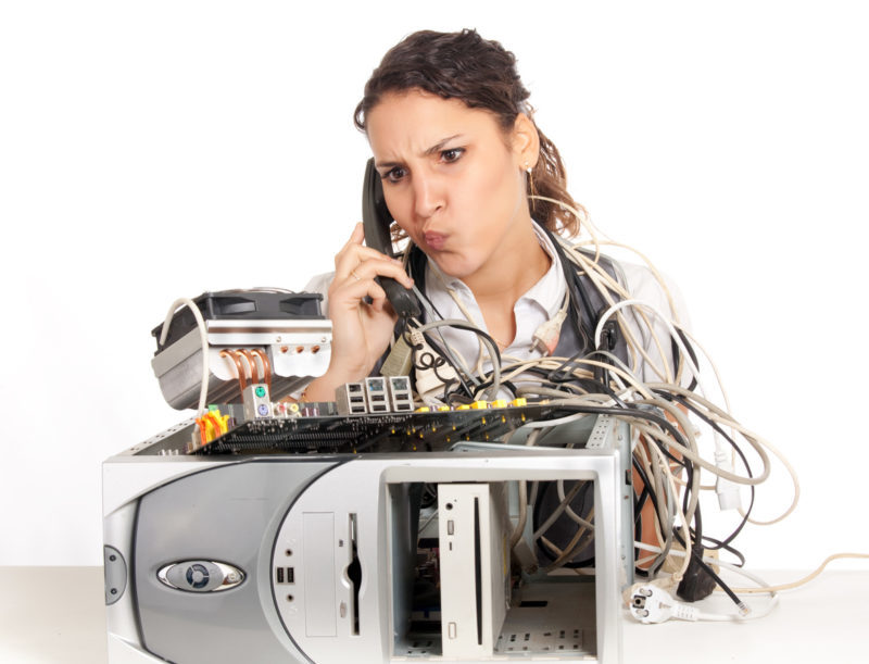 Woman on the phone looking confused at a broken computer