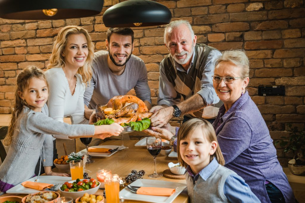 Happy multi-generation family holding Thanksgiving turkey together at dining table.