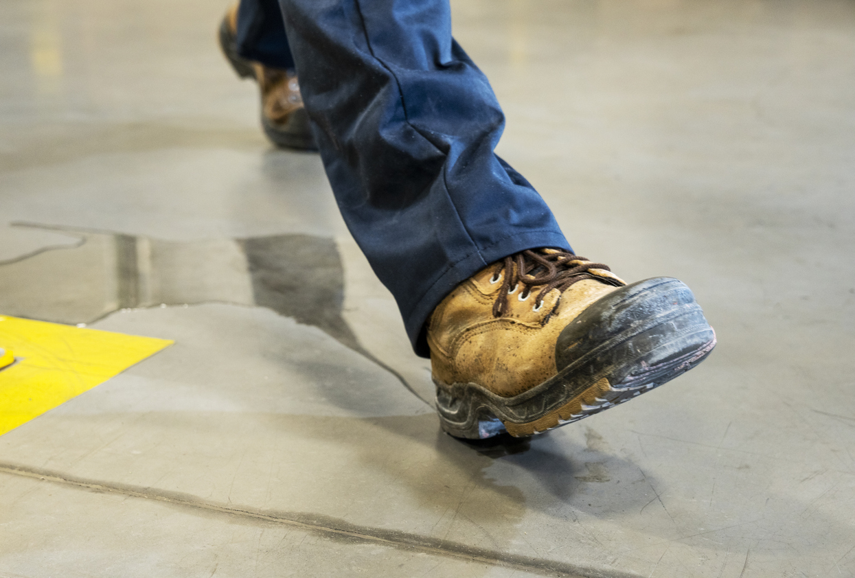 An industrial, manufacturing, safety topic. A worker slipping on liquid.