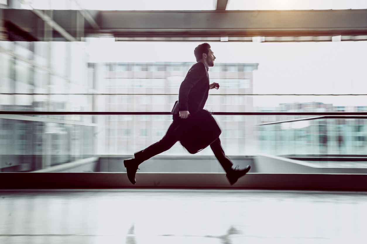 Businessman Running Along The Corridor