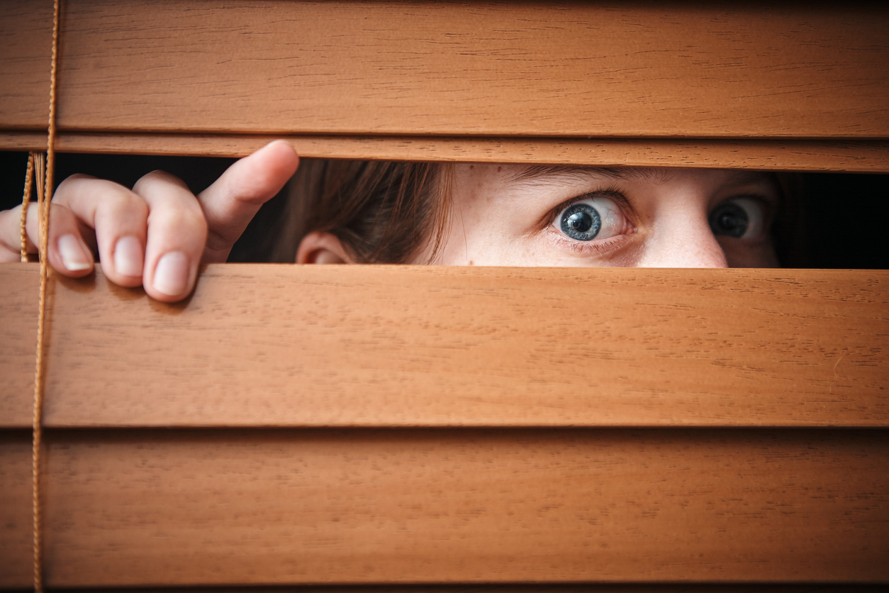 Terrified young woman peeps through wooden venetian blind