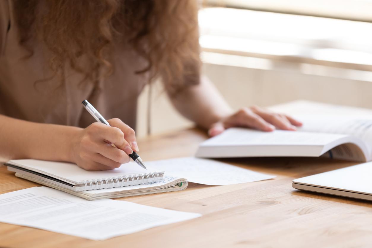 Close up of female student study using handbooks writing notes