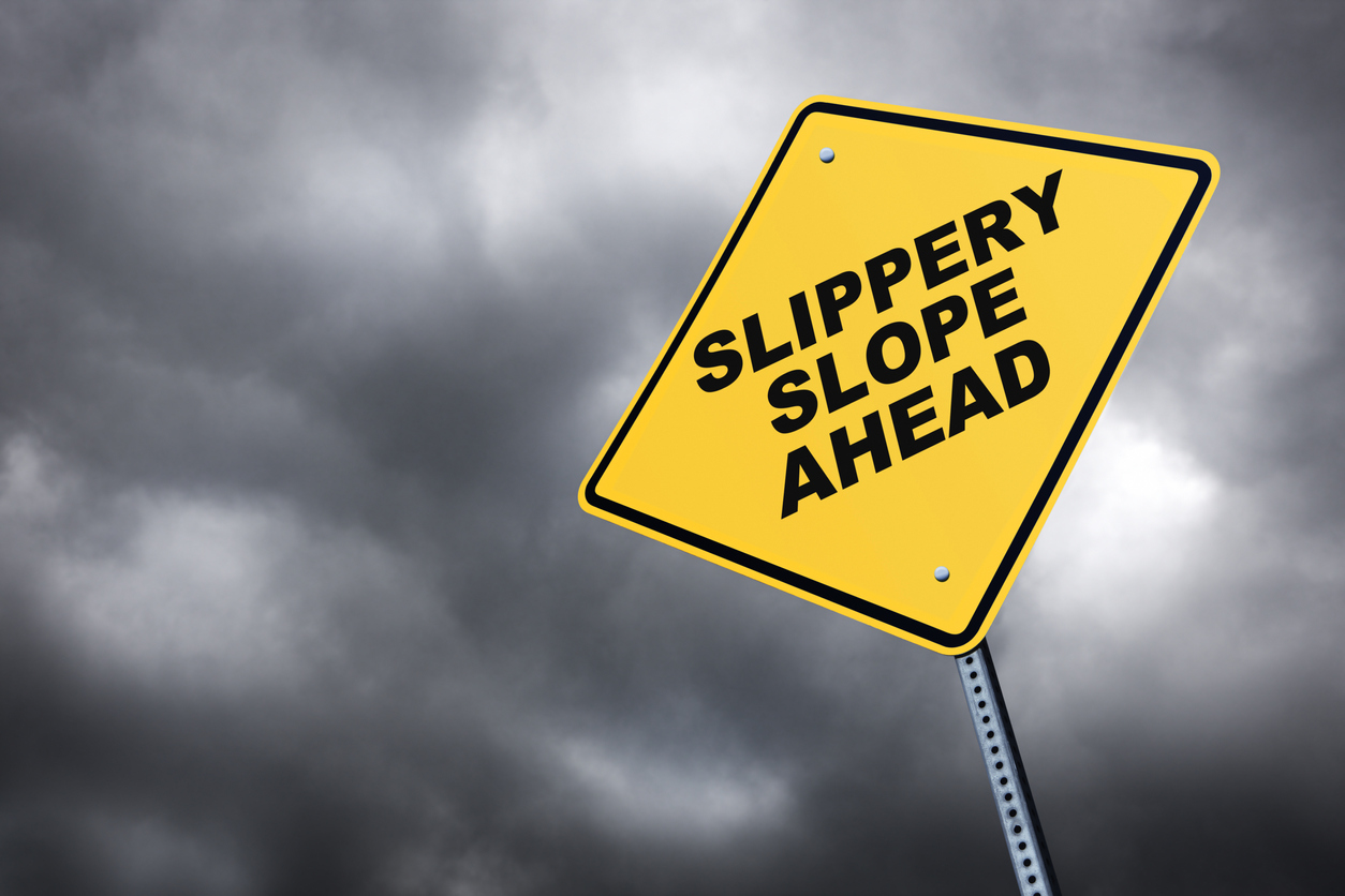 Slippery Slope road sign in front of cloudy sky background