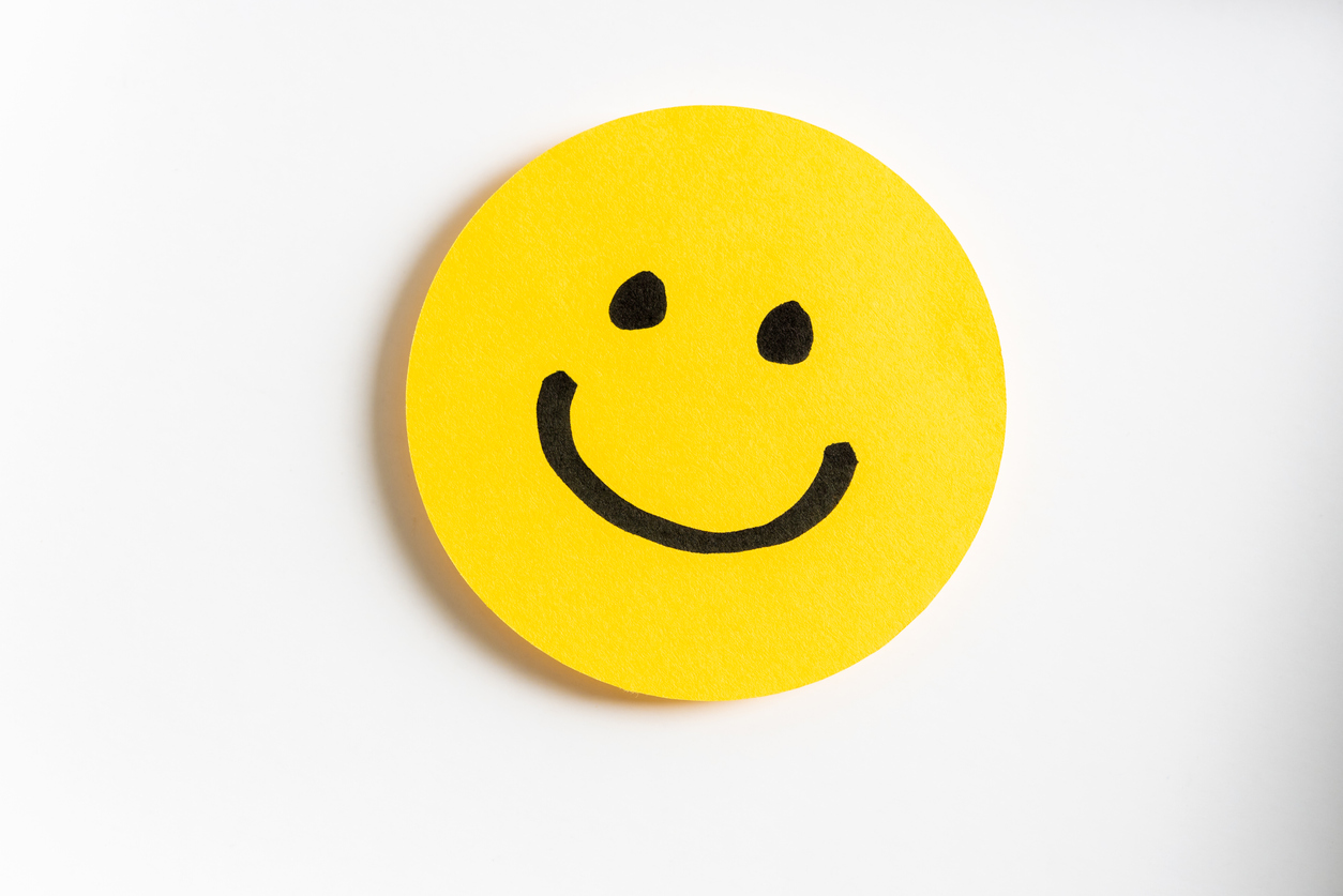 Drawing of a happy smiling emoticon on a yellow paper and white background.