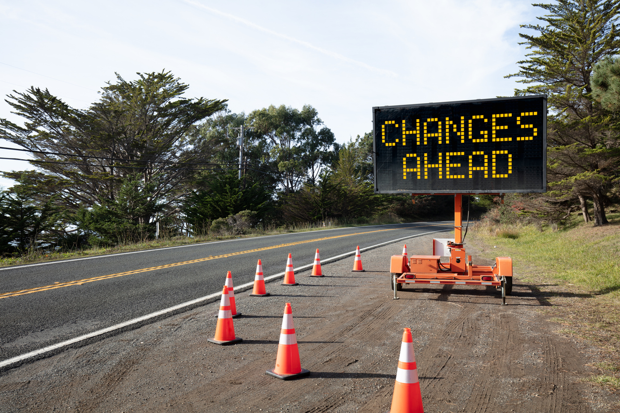 CHANGES AHEAD: Roadside sign: Trailer mobile warning sign parked by road with words for safety by orange cones