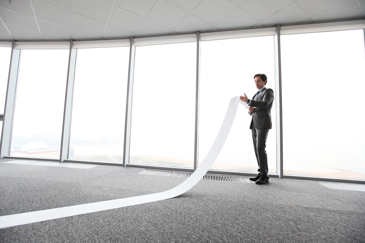 Businessman reading long paper list